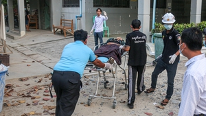 A wounded man on a stretcher after police and military opened fire on protesters in Mandalay yesterday