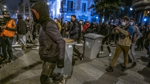 Protesters dragging bins during clashes with police officers on Vía Laietana