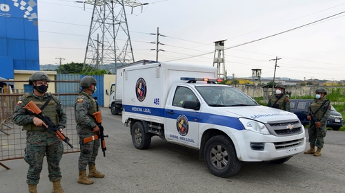 Members of the military guard the prison in Guayaquil as a prisoner's body is removed