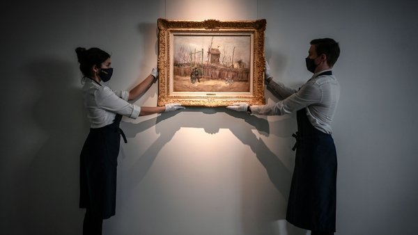 The painting depicts a man and woman strolling arm in arm past a ramshackle fence with a windmill in the background