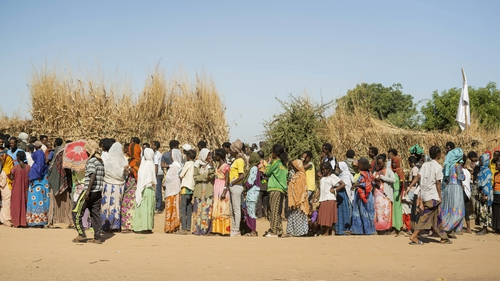 Ethiopian refugees from Tigray region wait in line to receive aid at the Um Rakuba refugee camp in Sudan