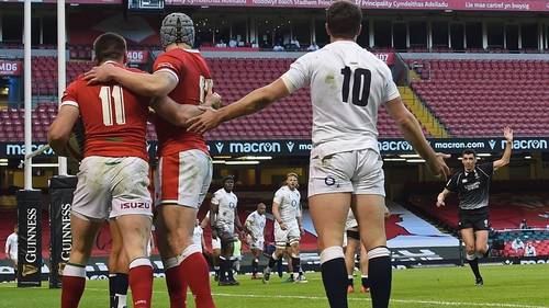 Wales' Josh Adams (L) is congratulated by Jonathan Davies as England's George Ford appeals to referee Pascal Gauzere