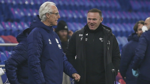Mick McCarthy and Wayne Rooney share some touchline banter during Tuesday night's game