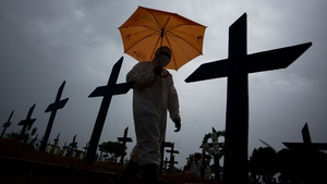 A worker wearing a protective suit walks past the graves of Covid-19 victims at a cemetery in the city of Manaus