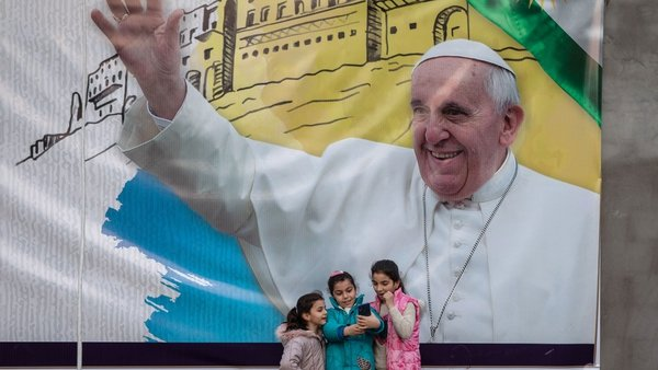 Young girls take a selfie in front of a poster promoting the upcoming trip of Pope Francis in Erbil