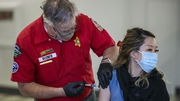 Reserve Deputy Chuck Rozner administers a Covid-19 shot to Janett Tsay at a mobile vaccination site in Los Angeles