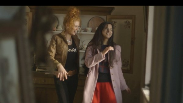 A scene from Town of Strangers: Chloe and her friend trying out dance moves