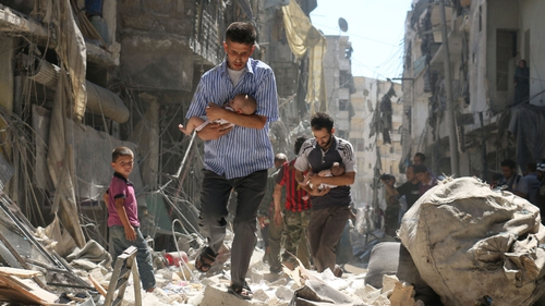 Syrian men carrying babies make their way through the rubble after an air strike in Aleppo in September 2016