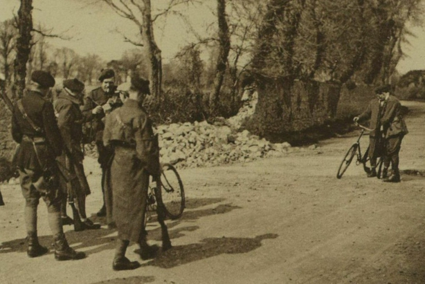 Auxiliaries searching a civilian on a bicycle at the site of a foiled ambush Photo: Illustrated London News [London, England], 19 April 1921
