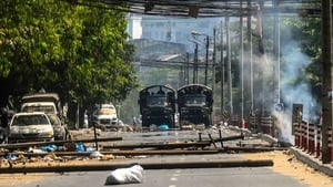 Military trucks are seen near the remains of a barricade erected by protesters in the city of Yangon