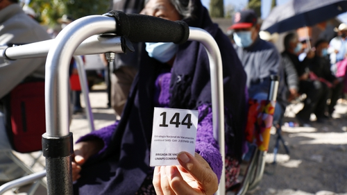 A woman shows her number in the queue for a Covid vaccine in Leon, Mexico