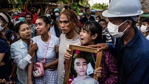 The family of a 25-year-old killed during protests in Yangong hold his photo at his funeral