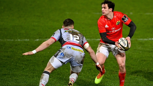 Joey Carbery of Munster in action against Scarlets' Steff Hughes