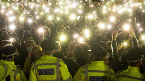 People in the crowd turn on their phone torches as they gathered in Clapham Common in London