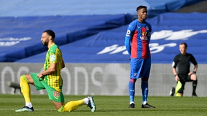 Wilfried Zaha stands as players and officials 'take the knee'