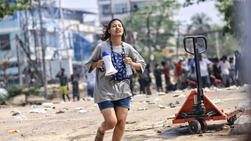 A woman holds a megaphone during a protest in Hlaing Tharyar township