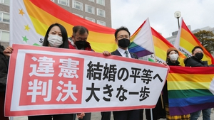 Lawyers for the plaintiffs, surrounded by rainbow flags, held up a sign declaring the ruling 'a huge step towards equality in marriage'