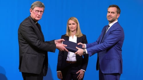 Lawyer Kerstin Stirner looks on as Bjoern Gercke hands the report to Archbishop Rainer Maria Woelki (L)