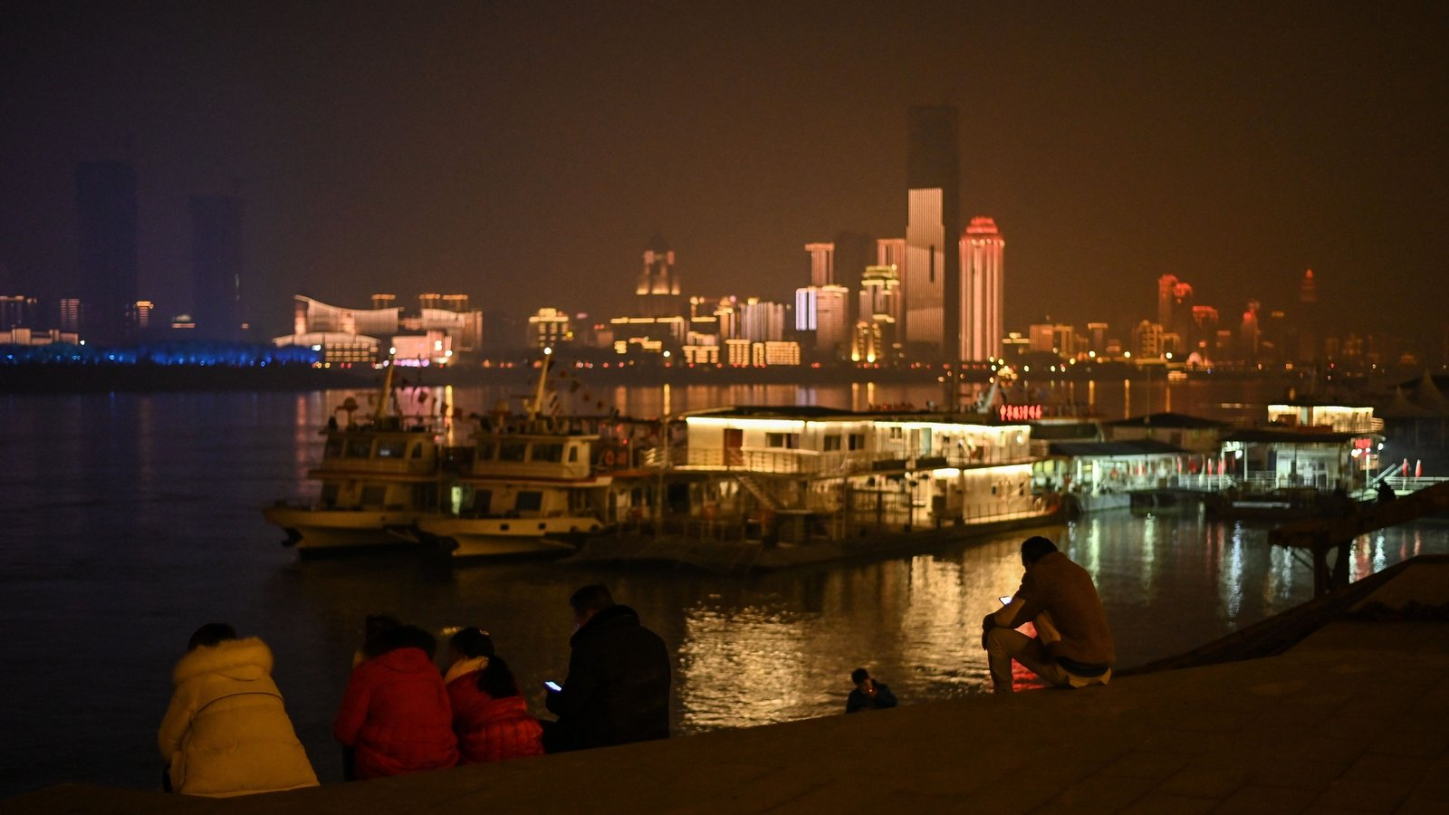 Image - People sit on the banks of the Yangtze River in the central Chinese city of Wuhan