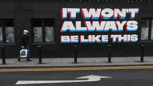 A man walks past a mural by Emmalene Blake in Dublin city centre quoting a song title by rock band 'Inhaler'