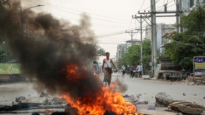 Debris burns during a protest in Mandalay