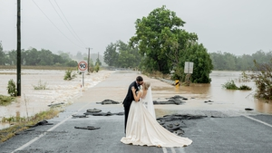An incredible photo shows the couple kissing in front of the flooded bridge that blocked her from completing the five minute drive into the town (Pic: Amanda Hibbard)