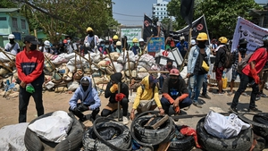 Protesters gather by a barricade in Yangon