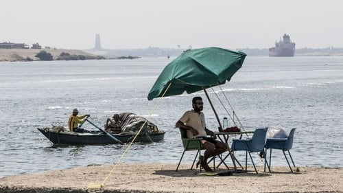 A fisherman takes a rest as a cargo ship sails through the Suez Canal in 2019
