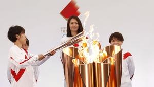 Azusa Iwashimizu (L), a member of Japan women's football national team, lights the torch from the celebration cauldron in Fukushima