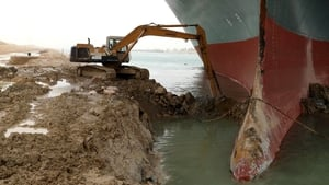 A digger extracts sand from around the Ever Given vessel which ran aground diagonally across the Suez Canal on Tuesday morning