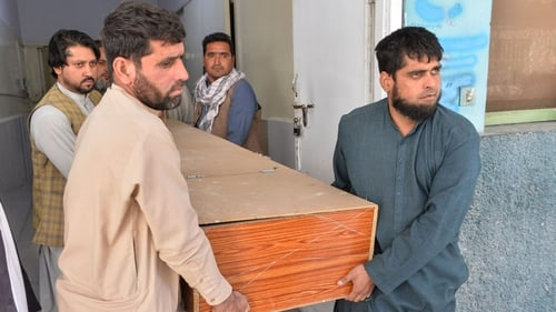 Relatives transport the body of one of the polio workers who was shot dead in Jalalabad today