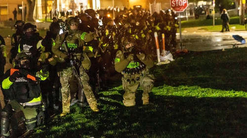 Minnesota state troopers prepare to fire tear gas at protesters