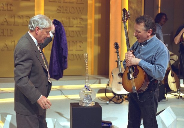 Broadcaster Gay Byrne and his guest, musician Dónal Lunny, on RTÉ Television's 'The Late Late Show' in April 1996. Byrne is on the left of shot, presenting a crystal trophy to Lunny. Photo by Thomas Holton