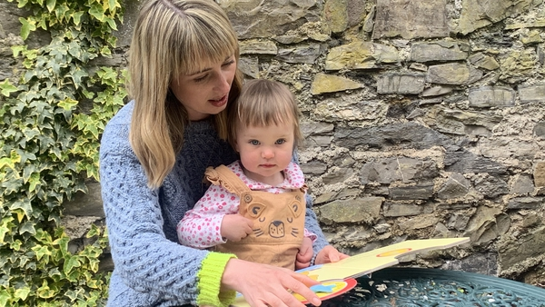 Dairíne McCafferty reads to her one-year-old daughter Riadh McCafferty Brannigan