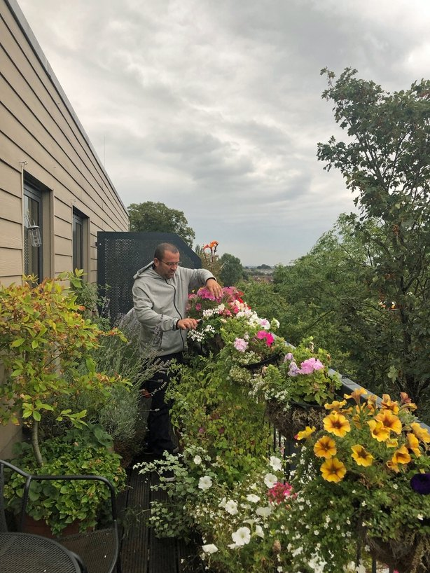 Garden Organic's Chris Collins looks after the hanging plants on his balcony (Garden Organic/PA)