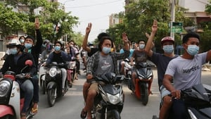 Demonstrators on motorcycles flash the three-finger salute during an anti-military coup protest in Mandalay