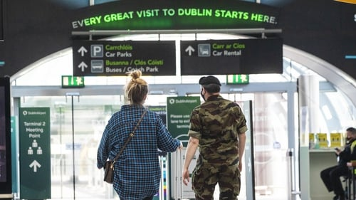 A member of the Defence Forces escorts a passenger from the Terminal 2 arrivals hall at Dublin Airport