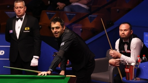 Ronnie O'Sullivan reacts after playing a shot as Mark Joyce (R) looks on