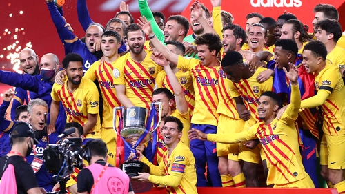 Barcelona captain Lionel Messi poses with the trophy in front of his team-mates