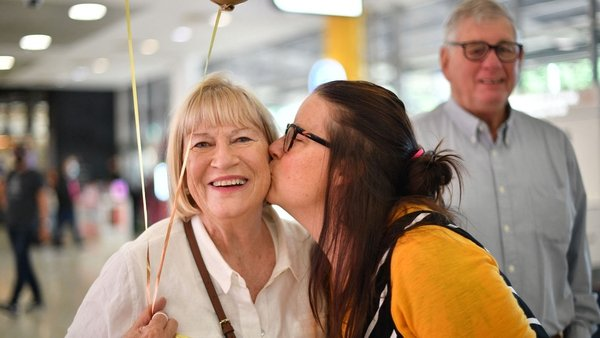 A family reunites after a flight from New Zealand lands at Sydney International Airport