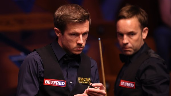 Jack Lisowski (L) chalks the cue as Allister Carter of England looks on