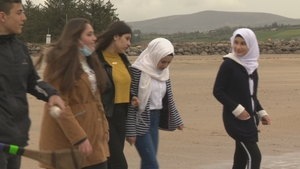 Eman and Amany walk on the beach with friends