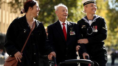 A war veteran is assisted as he walks down Elizabeth Street during the ANZAC Day parade in Sydney