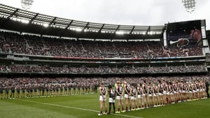 Essendon and Collingwood players line up in front of full stands at the Melbourne Cricket Ground