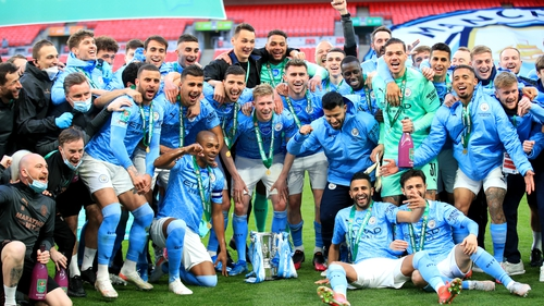 City players and staff celebrate with the trophy