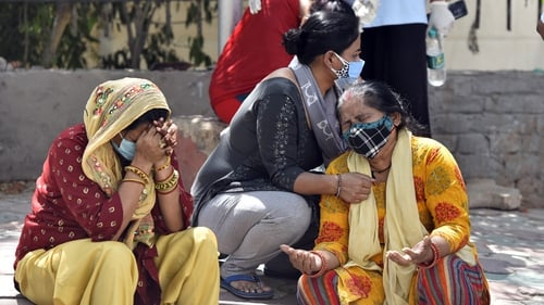 Grieving relatives of Covid victims wait outside a mortuary in New Delhi, India