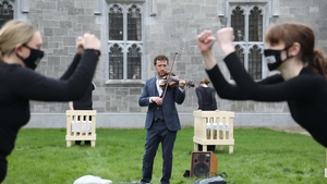 Colm Mac Con Iomaire plays the violin while students Leanne Anderson and Sarah Dooley perform to Emer's Dream inside the Quadrangle Building at NUI Galway. Photo: Aengus McMahon.