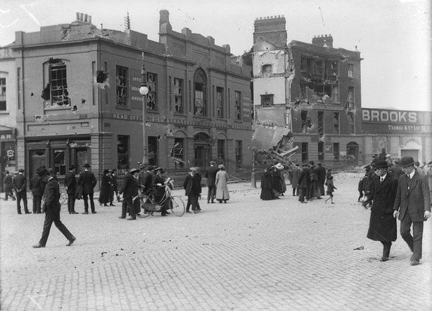 The ruins of Liberty Hall in the wake of the Easter Rising, Beresford Place, Dublin 1916. There are people walking in the foreground.