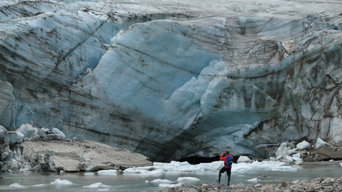 A visitor photographs a photo of a wall of ice of the Pasterze glacier in Austria