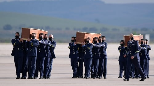 The coffins were taken off the plane by soldiers at the airport